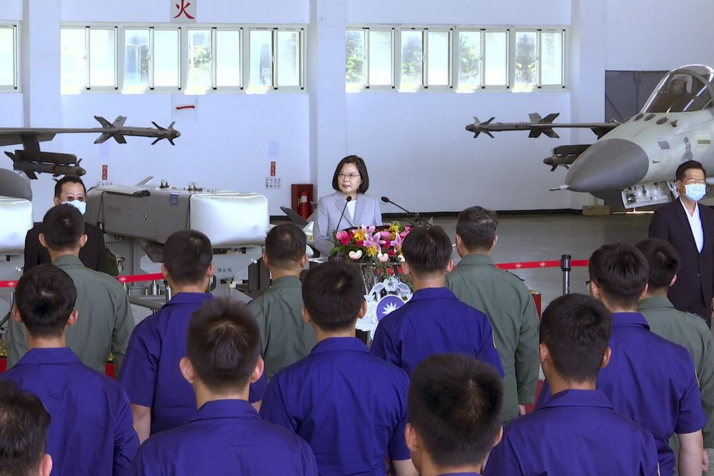 Taiwan President Tsai Ing-wen, center, speaks near Taiwan's Indigenous Defense Fighter (IDF) jets displayed during a visit to the Penghu Magong military air base in outlying Penghu Island, Taiwan Tuesday, Sept. 22, 2020. Tsai visited the military base on one of Taiwan's outlying islands Tuesday in a display of resolve following a recent show of force by rival China. (AP Photo/Johnson Lai)