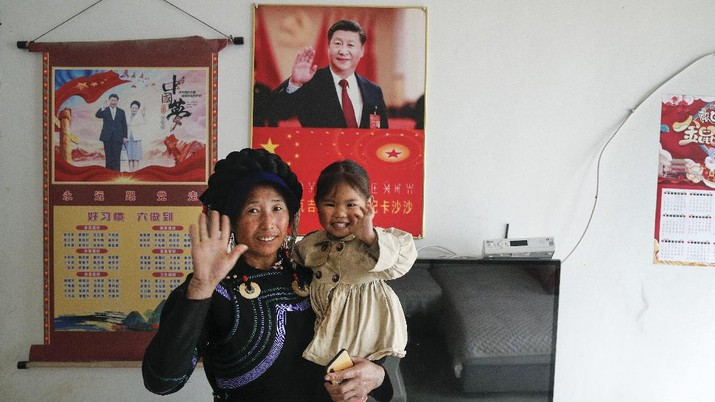 A Yi ethnic minority member stands inside his house displaying posters of Chinese President Xi Jinping and his wife Peng Liyuan, in Xujiashan village in Ganluo County, southwest China's Sichuan province, on Sept. 10, 2020. Communist Party Xi's smiling visage looks down from the walls of virtually every home inhabited by members of the Yi minority group in a remote corner of China's Sichuan province. Xi has replaced former leader Mao Zedong for pride of place in new brick and concrete homes built to replace crumbling traditional structures in Sichuan's Liangshan Yi Autonomous Prefecture, which his home to about 2 million members of the group. (AP Photo/Andy Wong)