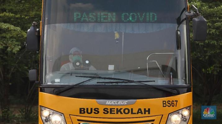 Petugas melakukan penguapan dengan liquid disinfektan ke bus sekolah yang digunakan untuk mengevakuasi pasien Covid-19 berstatus OTG (Orang Tanpa Gejala) di Posko Gabungan PSBB dan Gakplin Protkes, Kramat Jati, Jakarta Timur. (CNBC Indonesia/Andrean Kristianto)