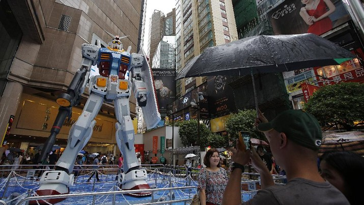 A man takes photos of a 1/3 scale model of the giant robot Gundam, made of steel and fabric glass, displayed during an exhibition in Hong Kong's Times Square Friday, Aug. 2, 2013. The 2-ton (4.409-pound) and 6-meter (19-foot, 7-inch)-tall figure is said to be the largest Gundam ever showcased outside of Japan. (AP Photo/Vincent Yu)