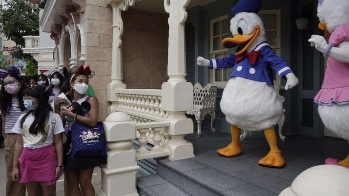 Visitors wearing face masks line up to take photos with the iconic cartoon characters Donald Duck and Daisy Duck at the Hong Kong Disneyland, Friday, Sept. 25, 2020. Hong Kong Disneyland reopened its doors to visitors after closed temporarily due to the coronavirus outbreak. (AP Photo/Kin Cheung)