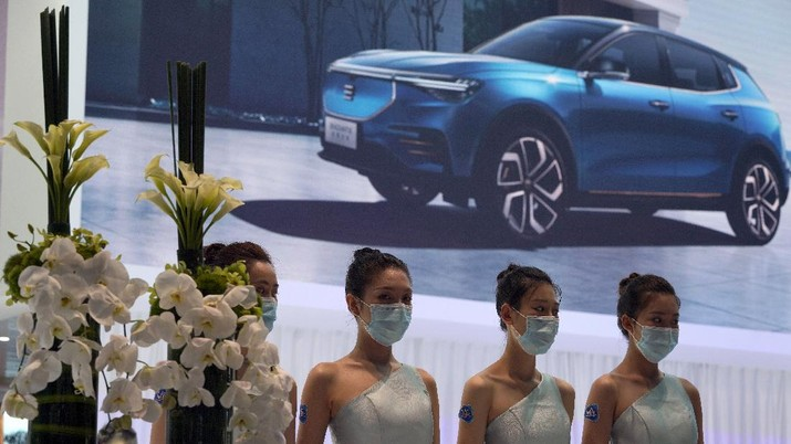 Receptionists with Chinese automaker Enovate waits for attendees of the Auto China 2020 show in Beijing on Saturday, Sept. 26, 2020. Ford, Nissan and BMW unveiled electric models with more range for China on Saturday as the Beijing auto show opened under anti-virus controls that included holding news conferences by international video link.(AP Photo/Ng Han Guan)