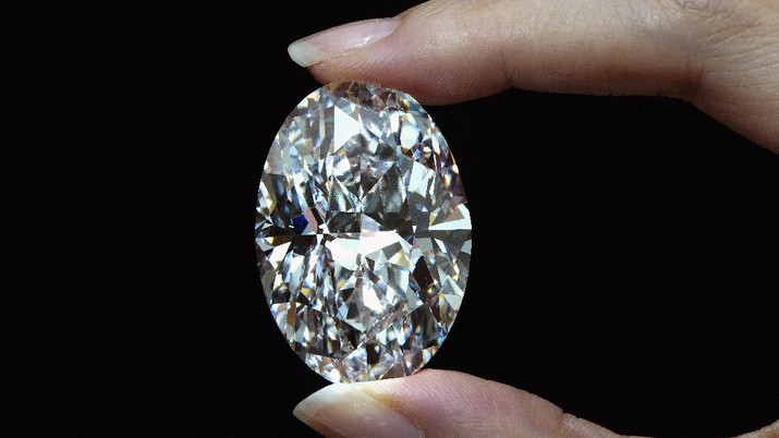A 102.39 carat, D color, flawless diamond is displayed by a model at a Sotheby's auction room in Hong Kong Monday, Sept. 28, 2020. It is the first time that a diamond this size and caliber will be actioned without reservations in history. (AP Photo/Vincent Yu)