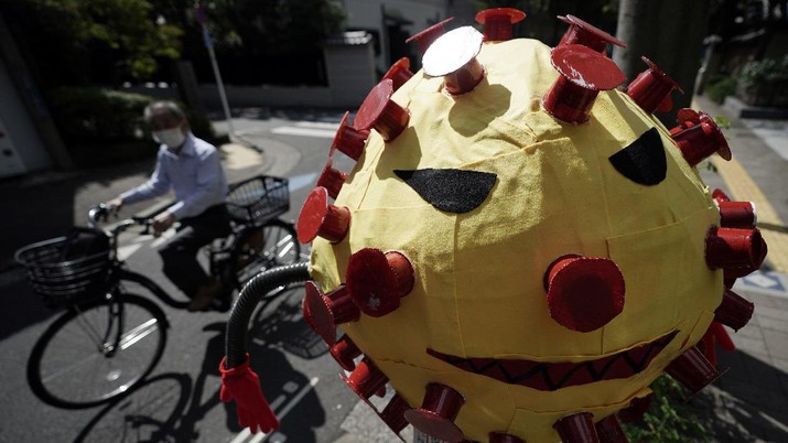A man wearing a protective mask to help curb the spread of the coronavirus rides a bicycle past a scarecrow depicting coronavirus displayed at a street Monday, Sept. 28, 2020, in Tokyo. The Japanese capital confirmed more than 70 coronavirus cases on Monday. (AP Photo/Eugene Hoshiko)