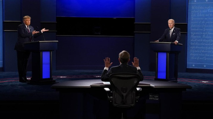 Moderator Chris Wallace of Fox News, center, gesturing during the first presidential debate between President Donald Trump, left, and Democratic presidential candidate former Vice President Joe Biden, right, Tuesday, Sept. 29, 2020, at Case Western University and Cleveland Clinic, in Cleveland, Ohio. (AP Photo/Patrick Semansky)