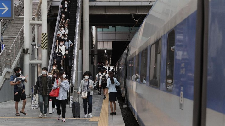 People wearing face masks to help protect against the spread of the coronavirus prepare to board a train ahead of the upcoming Chuseok holiday, the Korean version of Thanksgiving Day, at the Seoul Railway Station in Seoul, South Korea, Tuesday, Sept. 29, 2020. (AP Photo/Ahn Young-joon)