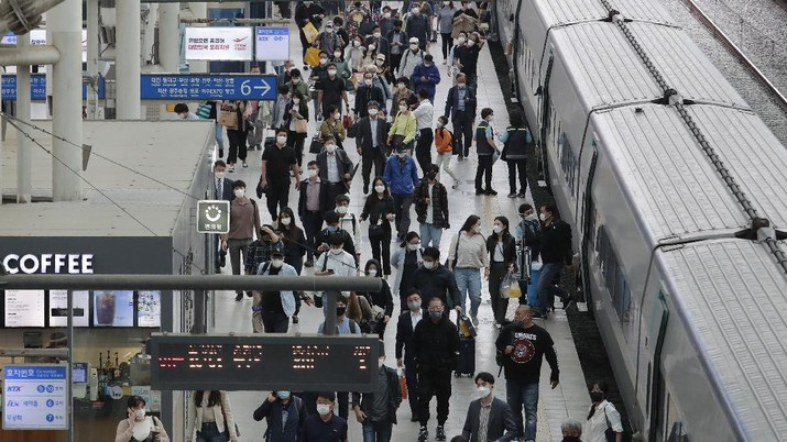 People wearing face masks to help protect against the spread of the coronavirus exit a train ahead of the upcoming Chuseok holiday, the Korean version of Thanksgiving Day, at the Seoul Railway Station in Seoul, South Korea, Tuesday, Sept. 29, 2020. (AP Photo/Ahn Young-joon)