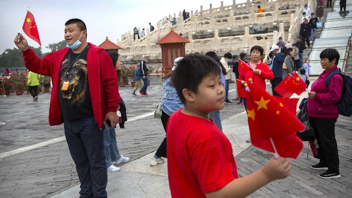 Visitors pose with Chinese flags at the Temple of Heaven in Beijing, Thursday, Oct. 1, 2020. Millions of Chinese tourists usually would use their week-long National Day holidays to travel abroad. This year, travel restrictions due to the coronavirus pandemic mean that some 600 million tourists - about 40% of the population - will travel within China during the holiday that began Thursday, according to Ctrip, China's largest online travel agency (AP Photo/Mark Schiefelbein)