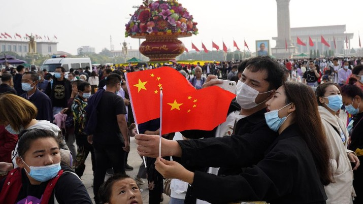 Visitors wearing masks to protect from coronavirus hold for Chinese flags for a photo as they visit Tiananmen Square during National Day in Beijing on Thursday, Oct. 1, 2020. Millions of Chinese tourists usually would use their week-long National Day holidays to travel abroad. This year, travel restrictions due to the coronavirus pandemic mean that some 600 million tourists - about 40% of the population - will travel within China during the holiday that began Thursday, according to Ctrip, China's largest online travel agency. (AP Photo/Ng Han Guan)