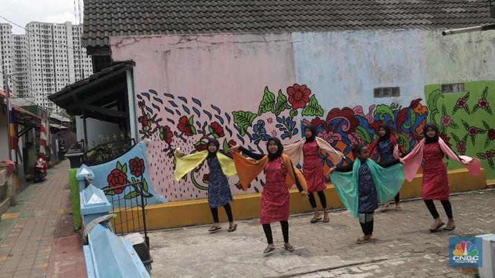 Sejumlah pelajar belajar menari di Kawasan Kampung Batik, Cibuluh, Bogor, Jawa Barat, Jumat (2/10). Pandemi Covid 19 yang berdampak hampir semua bidang ekonomi di Indonesia khususnya, tak terkecuali pariwisata di wilayah Bogor telah membuat problematika tersendiri bagi para penggiat industri pariwisata di Bogor. Kampung Batik Cibuluh yang digadang  menjadi salah satu pengembangan wisata tematik terbaru di Kota Bogor khususnya, berinisiasi tetap membangun semangat dan kreatifitas untuk sektor pariwisata dan industri Usaha Kecil Menengah ditengah berbagai dampak Covid 19 yang tengah di alami masyarakat kota Bogor. Kampung Batik Cibuluh bertujuan untuk menciptakan peluang dan membantu ekonomi warga dengan mengangkat potensi wilayah yang ada salah satunya batik yang awalnya terfokus pada pemberdayaan kaum ibu sebagai bentuk dukungan terhadap keseteraan gender di Indonesia. Kampung Batik cibuluh ini terbentuk atas peran serta dukungan dari para tokoh masyarakat, pemuda-pemudi kampung cibuluh, pemerintah kota bogor, dan para stakeholder terkait yaitu Baznas dan IPB. Melalui peran serta masyarakat, Kampung Neglasari, Kelurahan Cibuluh akan dipercantik dengan berbagai hiasan batik, seperti perbaikan gapura, pembuatan mural, pembanguan area kaulinan anak, area kuliner, area foto instagramable, museum batik, dan area belajar membatik.(CNBC Indonesia/ Muhammad Sabki)