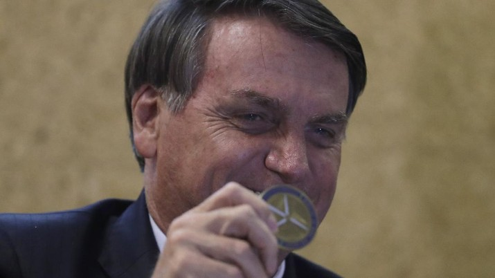 Brazil's President Jair Bolsonaro shows a Niobium coin, which he received as a gift during the launch of the Mining and Development Program, at the headquarters of the Ministry of Mines and Energy, in Brasilia, Brazil, Monday, Sept. 28, 2020. (AP Photo/Eraldo Peres)