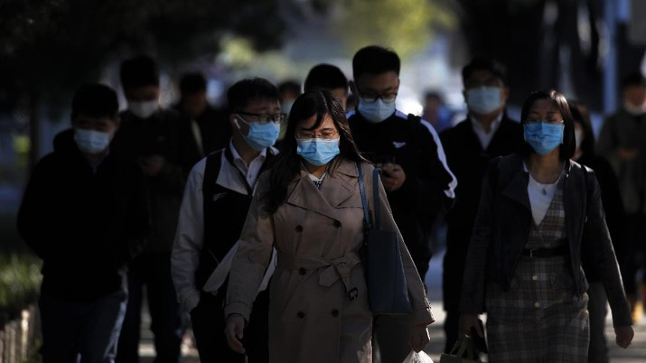People wearing face masks to help curb the spread of the coronavirus walk on a street during the morning rush hour in Beijing, Monday, Oct. 12, 2020. Even as China has largely controlled the outbreak, the coronavirus is still surging across the globe with ever rising death toll. (AP Photo/Andy Wong)