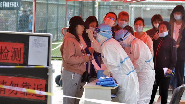 A medical staff takes a swab from a woman as residents line up for the COVID-19 test near the residential area in Qingdao in east China's Shandong province, Monday, Oct. 12, 2020. China's government says all 9 million people in the eastern city of Qingdao will be tested for the coronavirus this week after nine cases linked to a hospital were found. The announcement Monday broke a string of weeks without any locally transmitted infections reported in China. (Chinatopix via AP)