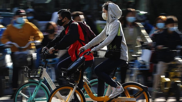 People wearing face masks to help curb the spread of the coronavirus ride bicycle during the morning rush hour in Beijing, Monday, Oct. 12, 2020. Even as China has largely controlled the outbreak, the coronavirus is still surging across the globe with ever rising death toll. (AP Photo/Andy Wong)