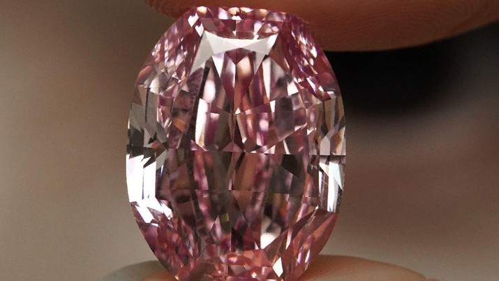 A model displays an ultra-rare 14.83-carat diamond that is one of the largest internally flawless fancy vivid purple-pink gem ever graded by the Gemological Institute of America at a Sotheby's auction room in Hong Kong Monday, Oct. 12, 2020. The diamond will be offered for sale in Geneva on Nov. 11, 2020. (AP Photo/Vincent Yu)