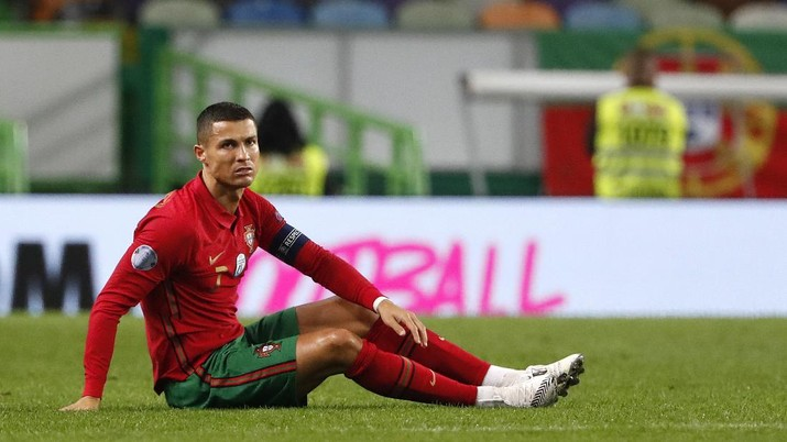FILE - In this Wednesday, Oct. 7, 2020 file photo Portugal's Cristiano Ronaldo, right, sits on the pitch during the international friendly soccer match between Portugal and Spain at the Jose Alvalade stadium in Lisbon. The Portuguese soccer federation says Cristiano Ronaldo has tested positive for the coronavirus. The federation says Ronaldo is doing well and has no symptoms. He has been dropped from the country's Nations League match against Sweden on Wednesday. (AP Photo/Armando Franca, File)