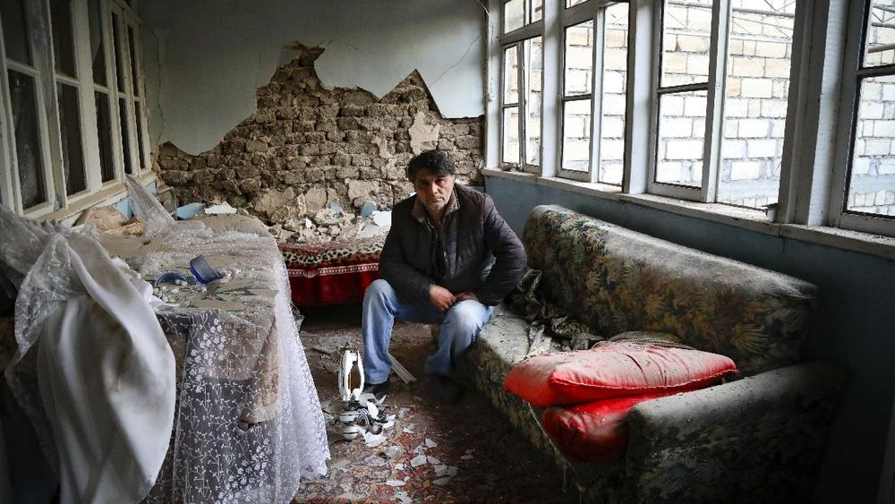 A man sits in his destroyed house in a residential area that was hit by rocket fire overnight by Armenian forces, early Saturday, Oct. 17, 2020, in Gyanga, Azerbaijan's second largest city, near the border with Armenia. (AP Photo/Aziz Karimov)