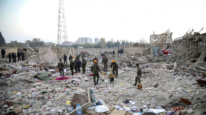 Soldiers and firefighters search for survivors in a residential area that was hit by rocket fire overnight by Armenian forces, early Saturday, Oct. 17, 2020, in Gyanga, Azerbaijan's second largest city, near the border with Armenia. (AP Photo/Aziz Karimov)