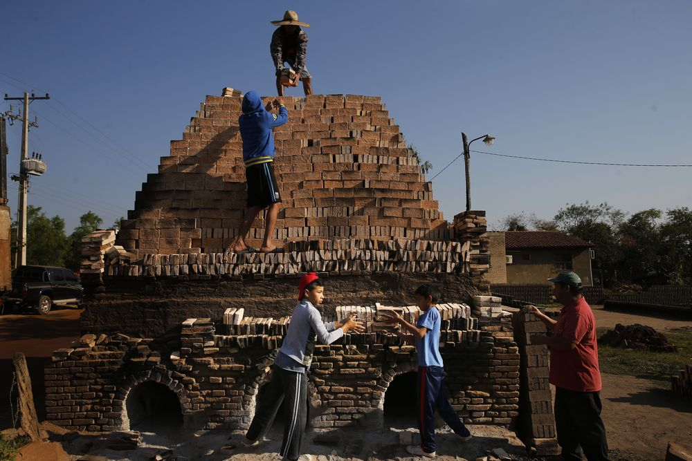 Children work with their relatives to load a kiln with clay bricks in Tobati, Paraguay, Friday, Sept. 4, 2020. In many of the small Tobati brick factories, locals begin to work at an early age to complement their family's income. (AP Photo/Jorge Saenz)