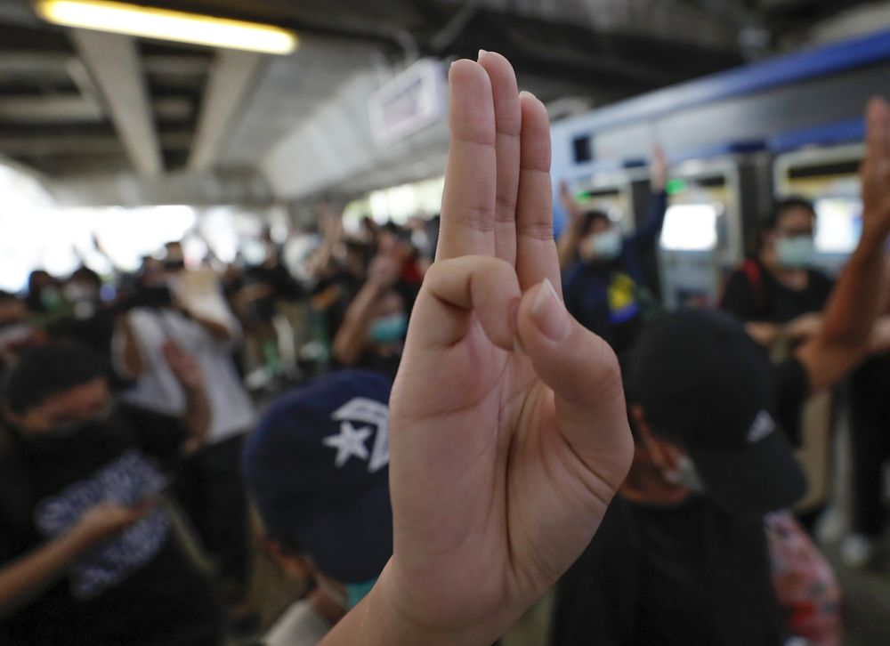 Pro-democracy protesters raise three-finger salutes, a symbol of resistance, during a protest at sky train platform in Bangkok, Thailand, Saturday, Oct. 17, 2020. The authorities in Bangkok shut down mass transit systems and set up roadblocks Saturday as Thailand's capital braced for a fourth straight day of determined anti-government protests. (AP Photo/Sakchai Lalit)