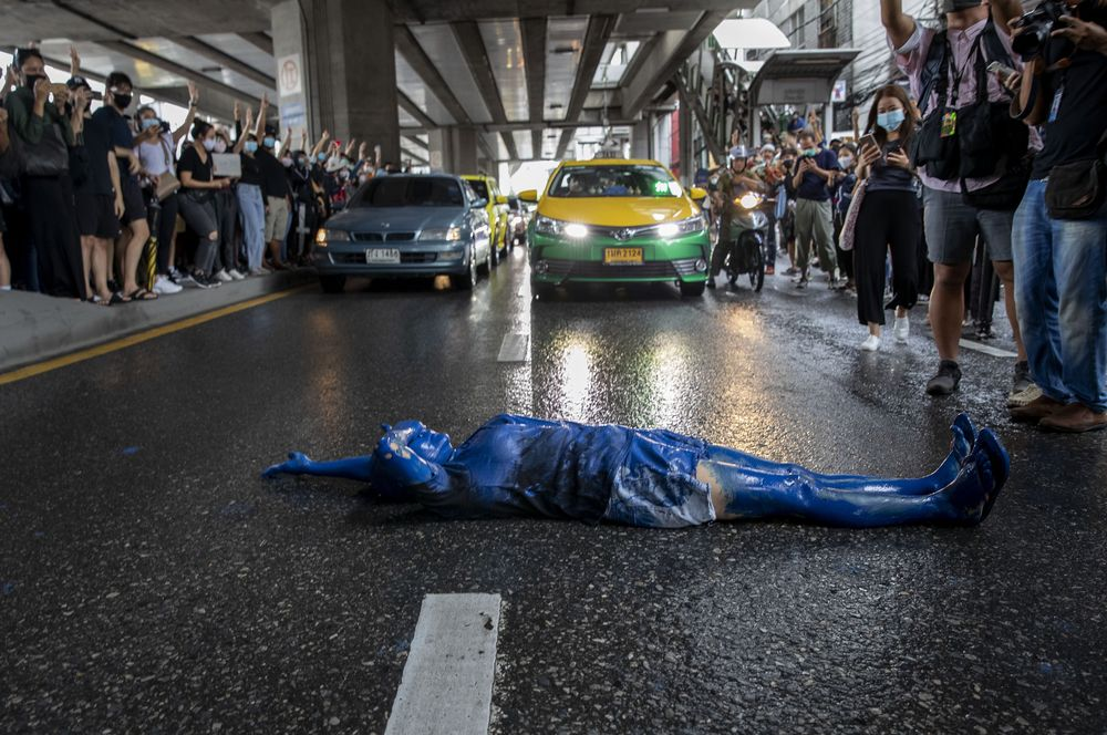 A pro-democracy protester covered in blue paint lies on a road during a protest in Udom Suk, suburbs of Bangkok, Thailand, Saturday, Oct. 17, 2020. The authorities in Bangkok shut down mass transit systems and set up roadblocks Saturday as Thailand's capital faced a fourth straight day of determined anti-government protests. (AP Photo/Gemunu Amarasinghe)
