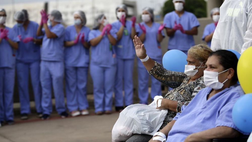 Medical workers celebrate as the last three patients are released from a field hospital at the National Stadium Mane Garrincha, after recuperating from COVID-19, in Brasilia, Brazil, Thursday, Oct. 15, 2020. (AP Photo/Eraldo Peres)