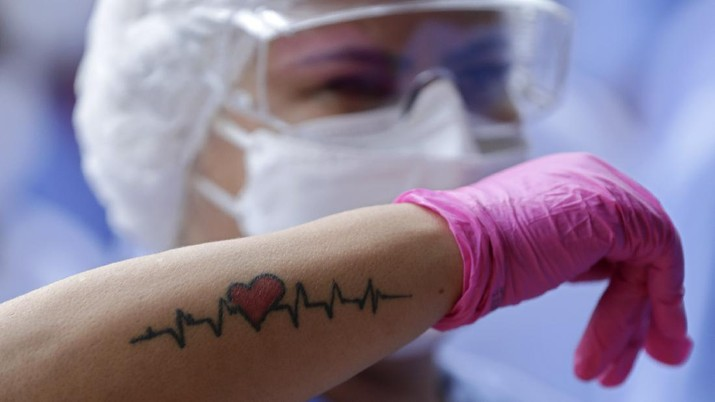 A medical worker shows her life sign tattoo while she and fellow workers celebrate as the last three patients are released from a field hospital at the National Stadium Mane Garrincha, after recuperating from COVID-19, in Brasilia, Brazil, Thursday, Oct. 15, 2020. (AP Photo/Eraldo Peres)