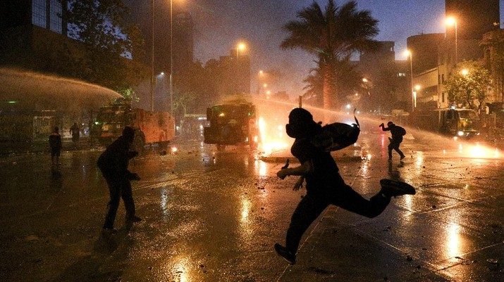 Demonstrators run as police uses water cannons to disperse them on the one-year anniversary of the start of anti-government mass protests over inequality in Santiago, Chile, Sunday, Oct. 18, 2020. (AP Photo/Esteban Felix)
