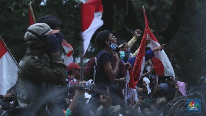 Aksi massa  yang menggelar demo menolak Omnibus Law UU Cipta Kerja menaiki Patung Kuda Arjuna Wiwaha yang berlokasi di Jalan Medan Merdeka Barat, Jakarta Pusat, Selasa (20/10). Mereka lalu mengibarkan bendera merah putih di patung tersebut. (CNBC Indonesia/Tri Susilo)