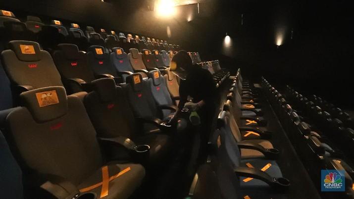 Petugas menyemprotkan cairan disinfektan di bangku bioskop yang akan dibuka hari ini di CGV Grand Indonesia Mall, Rabu (21/10/2020). Pemerintah Provinsi DKI Jakarta telah mengeluarkan surat keputusan untuk operasi bioskop-bioskop di Jakarta. Beberapa bioskop akan mulai memutar film hari ini. Pantauan CNBC Indonesia pada jam 12.00 belum ada penonton yang datang, kemudian pihak pengelola mengatur ulang jadwal agar jam 15.00 sudah bisa memulai pemutaran film.  Terlihat hanya beberapa warga saja yang mulai memesan tiket di tiket box. (CNBC Indonesia/ Tri Susilo)