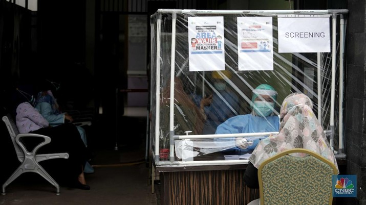 Dokter memperagakan proses vaksinasi saat simulasi pemberian vaksin di Puskesmas Depok, Jawa Barat, Kamis (22/10). Pemerintah Kota Depok akan menggelar simulasi pemberian vaksin corona. Pemberian vaksin idealnya sebanyak 60 persen dari jumlah penduduk Kota Depok. Adapun yang hadir bukanlah warga sungguhan yang hendak divaksin. Hanya perwakilan dari Pemkot Depok saja. Terdapat sejumlah tahapan alur yang akan diterapkan Pemerintah Kota Depok dalam pemberian vaksin. Orang yang masuk dalam kriteria mendapat vaksin akan diundang untuk datang ke puskesmas. Nantinya mereka duduk di ruang tunggu dengan penerapan protokol kesehatan. Mereka kemudian menunggu giliran dipanggil petugas. Setelah itu masuk ke ruangan untuk disuntik vaksin. Orang yang telah divaksin akan diregistrasi petugas guna memantau perkembangannya secara berkala.  (CNBC Indonesia/ Muhammad Sabki)