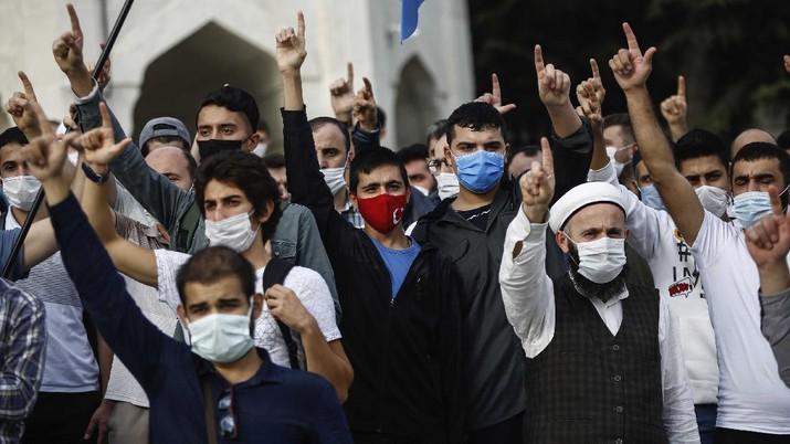 Seorang pria memegang gambar Macron dengan cetakan sepatu di atasnya ketika pengunjuk rasa Turki meneriakkan slogan-slogan menentang Prancis selama demonstrasi atas kartun Nabi Muhammad, di Istanbul. (AP/Adel Hana)