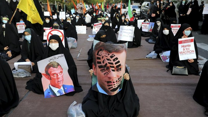 Iranian protesters hold defaced pictures of French President Emmanuel Macron during a protest against Macron and the publishing of caricatures of the Prophet Muhammad they deem blasphemous, in front of French Embassy in Tehran, Iran, Wednesday, Oct. 28, 2020. Macron has vowed his country will not back down from its secular ideals and defense of free speech. (AP Photo/Ebrahim Noroozi)