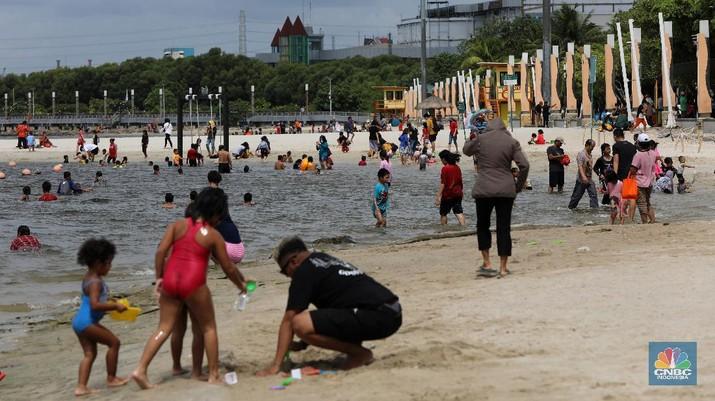 Wisatawan menikmati suasana Pantai Lagoon, Ancol, Jakarta, Jumat (30/10/2020). Libur Nasional dan Cuti bersama dimanfaatkan warga Jakarta untuk bertamasya ke tempat wisata di Jakarta.  (CNBC Indonesia/Andrean Kristianto)