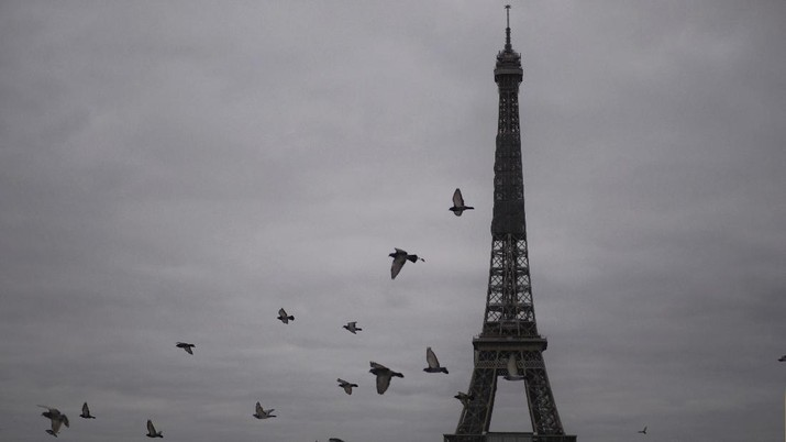 Pigeons fly next to the Eiffel Tower in Paris, Friday, Oct. 30, 2020. France re-imposed a monthlong nationwide lockdown Friday aimed at slowing the spread of the virus, closing all non-essential business and forbidding people from going beyond one kilometer from their homes except to go to school or a few other essential reasons. (AP Photo/Thibault Camus)