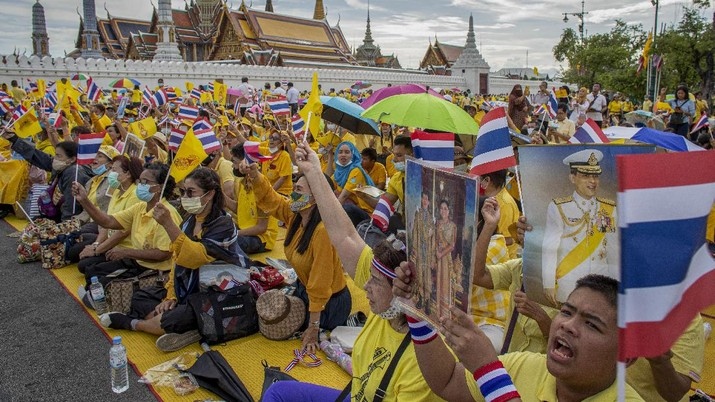 Supporters of the monarchy wave flags and display images of King Maha Vajiralongkorn, Queen Suthida and late King Bhumibol Adulyadej as they gather in front of the Grand Place in Bangkok, Thailand, Sunday, Nov. 1, 2020. Hundreds of royalists gathered close to the Grand Palace in which King Maha Vajiralongkorn is scheduled to visit for a Buddhist religious ceremony. (AP Photo/Wason Wanichakorn)