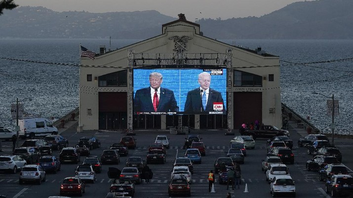 People watch from their vehicles as President Donald Trump, on left of video screen, and Democratic presidential candidate former Vice President Joe Biden speak during a Presidential Debate Watch Party at Fort Mason Center in San Francisco, Thursday, Oct. 22, 2020. The debate party was organized by Manny's, a San Francisco community meeting and learning place. (AP Photo/Jeff Chiu)