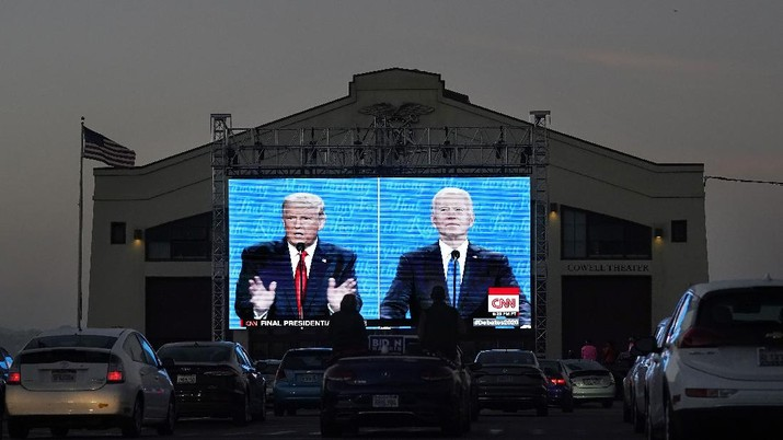 Elizabeth Allin, bottom center left, and Gideon Lett sit in a convertible while watching President Donald Trump, on left of video screen, and Democratic presidential candidate former Vice President Joe Biden speak during a Presidential Debate Watch Party at Fort Mason Center in San Francisco, Thursday, Oct. 22, 2020. The debate party was organized by Manny's, a San Francisco community meeting and learning place. (AP Photo/Jeff Chiu)