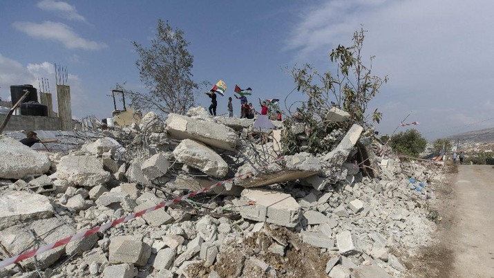 Palestinian children play on top of the demolished house of Khalil Dweikat, in the West Bank village of Rojeeb, east of Nablus, Monday, Nov. 2, 2020. The Israeli military said Monday its troops demolished the home of Dweikat, a Palestinian accused of killing an Israeli in a stabbing attack earlier this year. (AP Photo/Nasser Nasser)