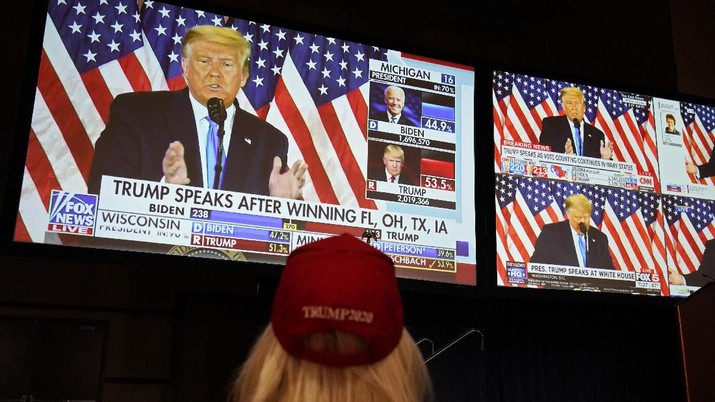 A live broadcast of President Donald Trump speaking from the White House is projected on screens at an election night party, Tuesday, Nov. 3, 2020, in Las Vegas. (AP Photo/John Locher)
