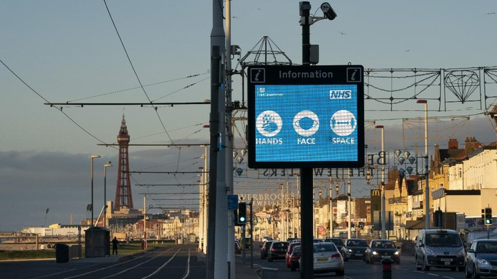 Public information Covid-19 signage is seen before Blackpool's annual Illuminations are lit for the last time before being switched off at midnight on Wednesday because of the four-week lockdown, in Blackpool, England, Wednesday Nov. 4, 2020. The illuminations were due to remain lit for an extra two months this season, until 3 January, to aid the town's tourism trade hit by Covid-19 restrictions. ( AP Photo/Jon Super)