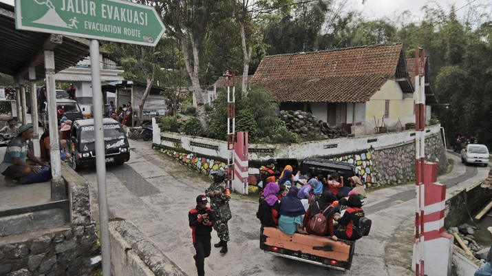 Villagers sit on the back of a truck as they are evacuated from their homes on the slope of Mount Merapi, in Krinjing, Central Java, Indonesia, Friday, Nov. 6, 2020. Indonesian authorities began evacuating people living on the volatile volcano's fertile slopes on Friday following an increase in volcanic activity. (AP Photo/Taufiq Rozzaq)