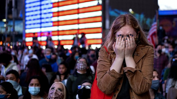 Fletcher Peters of New York, a journalism student at NYU, reacts as she watches President-elect Joe Biden on a monitor in Times Square Saturday, Nov. 7, 2020, in New York, as he addressed the nation. Peters said