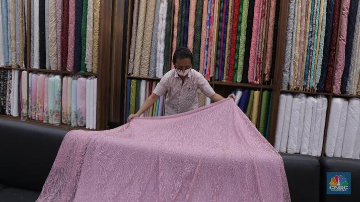 Pedagang beraktivitas di salah satu gerai kain di Pasar Mayestik, Jakarta, Rabu (11/11/2020). Pasar dalam negeri kembali dibanjiri oleh produk impor baik dalam bentuk kain maupun pakaian jadi di tengah lesunya industri domestik. Sengkarut industri tekstil terkait masalah impor masih belum berkesudahan. Saat ini ada tarik-tarikan kepentingan antara pelaku usaha industri soal mekanisme impor bahan baku yang efeknya bisa berbeda dari masing-masing industri hulu dan hilir. mengutip berita CNBC Indonesia pada 10 November, Kementerian Perdagangan dikabarkan bakal merevisi Peraturan Menteri Perdagangan (Permendag) mengenai aturan main importasi tekstil. Hal ini tidak lepas dari dorongan industri dalam negeri yang meminta adanya perubahan regulasi dari aturan-aturan yang lama. Maklum, beberapa revisi Permendag yang mengatur impor sejak tahun 2015 dinilai selalu pro barang impor. Pantauan CNBC Indonesia salah satu pemilik toko mengatakan bahwa bahan yang ia beli Grosiran di Bandung, Tasik dan sekitarnya. Namun tidak diketahui dari Mama bahan dasar tekstil itu berasal. Kalangan industri tekstil dan produk tekstil (TPT) termasuk di sektor hulu seperti benang masih mengeluhkan adanya gangguan produk impor. Masih ada persoalan tak harmoninya kebijakan sehingga ada industri yang kena dampak.  (CNBC Indonesia/Muhammad Sabki)