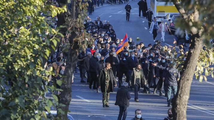 Protesters gather near the parliamentary building during a protest against an agreement to halt fighting over the Nagorno-Karabakh region, in Yerevan, Armenia, Wednesday, Nov. 11, 2020. Thousands of people flooded the streets of Yerevan once again on Wednesday, protesting an agreement between Armenia and Azerbaijan to halt the fighting over Nagorno-Karabakh, which calls for deployment of nearly 2,000 Russian peacekeepers and territorial concessions. Protesters clashed with police, and scores have been detained. (AP Photo/Dmitri Lovetsky)