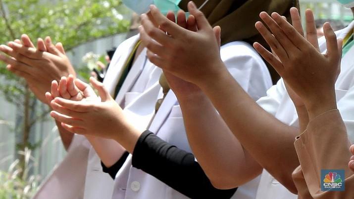 Sejumlah tenaga medis bertepuk tangan di Wisma Atlet Kemayoran, Jakarta, Kamis, 12/11. Tepuk tangan dilakukan untuk mengapresiasi para tenaga kesehatan di Hari Kesehatan Nasional. Hari Kesehatan Nasional yang ke-56 yang biasa diperingati setiap tanggal 12 November. Durasi 56 detik merujuk pada peringatan Hari Kesehatan Nasional (HKN) ke-56.Tepuk tangan itu diikuti oleh sejumlah petugas tenaga medis, Dokter, Perawat, TNI, Relawan Covid-19. Tepuk tangan 56 detik ini diimbau untuk dilakukan serentak pukul 12.00 WIB siang nanti. Kemenkes juga mengimbau momen tepuk tangan 56 menit itu diunggah di media sosial dan dilengkapi sejumlah tagar, di antaranya #gerakan56detik, #HKN56, hingga #terimakasihnakes. Dilihat di Twitter per pukul 08.00 WIB pagi ini, tagar #gerakan56detik telah memuncaki trending topic nasional. (CNBC Indonesia/ Muhammad Sabki)