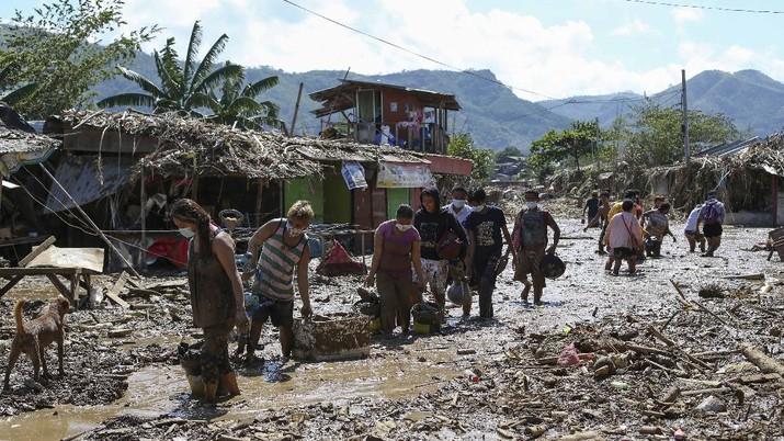 Warga menyelamatkan barang berharga yang masih bisa digunakan saat terkena banjir akibat terjangan Topan Vamco di Filipina. (AP/Aaron Favila)