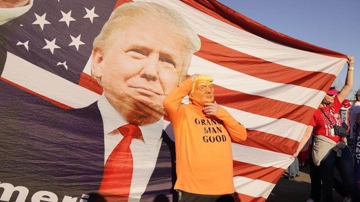 A person in a President Donald Trump mask poses for photos in front of a background with Trump on it as supporters attend pro-Trump marches, Saturday Nov. 14, 2020, in Washington. (AP Photo/Jacquelyn Martin)