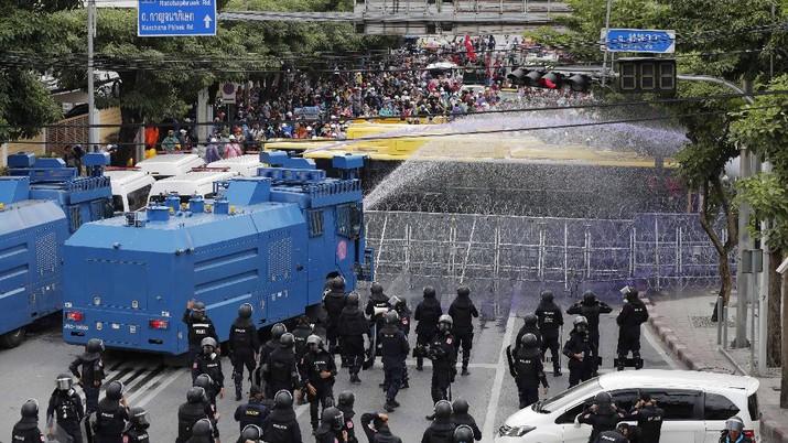 Polisi Thailand menembakan gas air mata kepada para demonstran yang mulai menembus barikade keamanan di depan kantor parlemen Thailand. (AP/Sakchai Lalit)