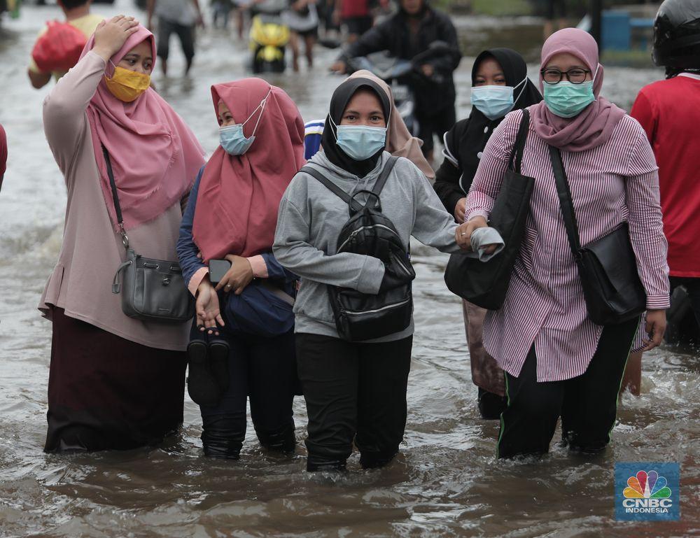 Warga melintasi genangan air rob di kawasan Pelabuhan Perikanan Muara Baru, Jakarta Utara, Selasa, (17/11/2020). (CNBC Indonesia/Muhammad Sabki)